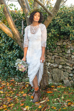 A beautiful model stands in a shaft of autumnal evening light , wearing a white cotton lawn Edwardian antique dress with Bedfordshire lace, broderie cut work, tape work and hand embroidered details. A crown of leaves and pastel rose bouquet complete the look.