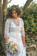 A beautiful model stands in a shaft of autumnal evening light , wearing a white cotton lawn Edwardian antique dress with Bedfordshire lace, broderie cut work, tape work and hand embroidered details
