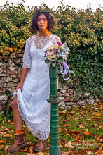 A beautiful model stands in a shaft of autumnal evening light , wearing a white cotton lawn Edwardian antique dress with Bedfordshire lace, broderie cut work, tape work and hand embroidered details. A unique bohemian bridal look with and Edwardian dress.