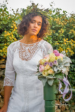 a model with dark, curly hair wears an antique lace wedding gown from the Edwardian era. A crown of laurels and pastel rose bouquet complete the look.