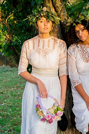 Two young women wear white Edwardian dresses and stand beneath a tree in a ray of golden autumnal sunshine. The central girl wears an original Edwardian white lace wedding dress with broderie anglais panels and hand embroidered details.