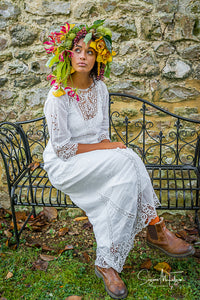 A pretty dark skinned model wears an oversized flower crown in sunset shades of yellow and pink. She is dressed in an antique  Edwardian lace wedding dress with brown leather boots, and is every inch the bohemian bride