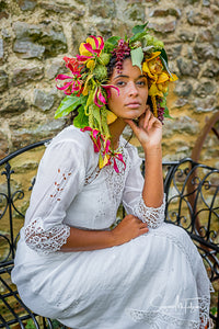 A pretty dark skinned model wears an oversized flower crown in sunset shades of yellow and pink. She is dressed in an Edwardian lace wedding dress. She looks every inch the beautiful boho bride