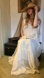 A boho hippy girl wears a long white flowing 1970's vintage dress and a straw hat. She sits on a vintage trunk with a flower crown in her lap