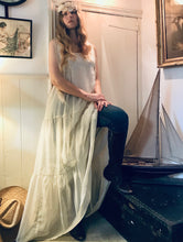 A quirky look - a hippy girl wears a long white flowing dress over jeans and boots