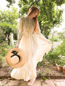 Full silk skirts swirl around the legs of a tall, elegant redhead. Sun filters through her silk skirts, and she carries a widebrimmed sunhat as she stands in an English Country Garden. The dress is Edwardian in style, and made with antique lace.