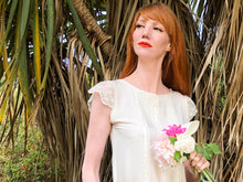 A beautiful willowy red head wears a cream silk 1920's style wedding dress. She stands against a palm tree, with a bouquet of peonies in her hand.