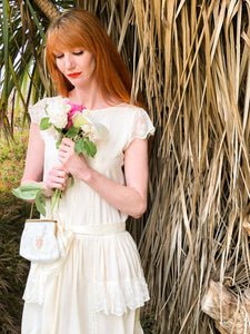 A redheaded model gazes down at a bouquet of peonies. She is stood against a palm tree, and wears a cream silk drop waisted dress with lace cap sleeves and a silk satin sash.