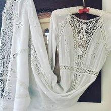 An original Edwardian white cotton lace is shown hung on a hanger. The dress has lace inserts at the bodice, hem, skirt and cuffs.