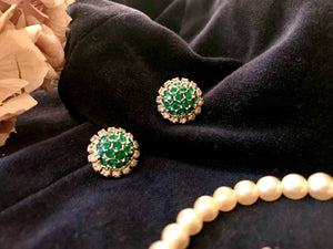 1950's diamante and green paste earrings - a dome of glittering green stones is surrounded by a circlet of twinkling white diamantes. The clip on earrings are shown against a black velvet background with pearls and dried hydrangeas