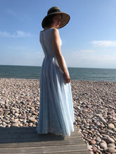 A young girl in a broad brimmed straw hat is backlit on a pebble beach. She wears a vintage fifties dress from Days of Grace in Budleigh Salterton.
