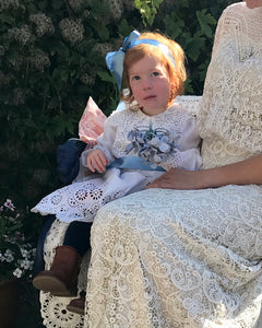 A redheaded toddler girl wears an edwardian bridesmaids dress of white lace