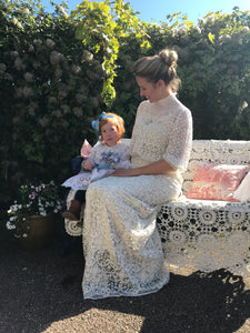 A Mother and child in edwardian dresses from days of Grace Vintage. The child is dressed in a Broderie Anglais dress with a blue satin alice band, just like a little Alice in Wonderland