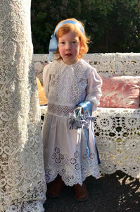 Alice in Wonderland style! A red haired toddler stands in an Edwardian bridesmaids dress made of crisp white cotton lace. She holds a bunch of blue silk flowers and has a blue satin alice band