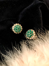 a pair of faux emerald vintage clip on earrings from the 1950's sparkle against black velvet and peachy feathers