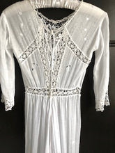 The back view of an edwardian lace dress, showing the tape fastenings and fine lace detailing