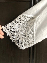 Close up the handmade bedfordshire lace and tape work cuff of an Edwardian wedding gown