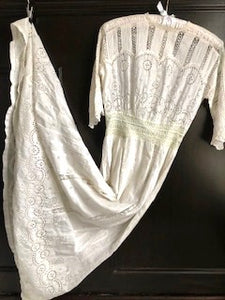 A stunning Edwardian white dress is shown on the hanger. The dress is extravagantly worked with broderie anglais and handmade lace, and is a beautiful example of the period. Perfect for a wedding gown.