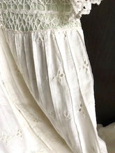 Close up of the hand made lace backed with pale green silk on the waistband of a white Edwardian dress made from cotton lawn