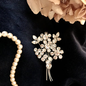 a spray of flowers formed from glittering white diamantes are mounted on a pin brooch - the original fifties brooch is sat on dark velvet, surrounded by a string of pearls and some flower petals