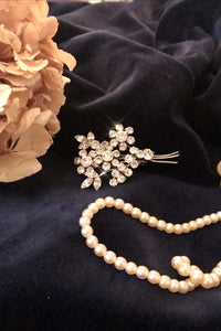 A pretty 1950's brooch - a sprig of white diamante flowers and leaves . Original 50's brooch with great sparkle
