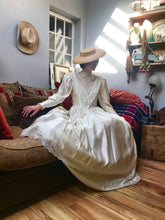 A romantic edwardian wedding dress with a full skirt, high neck and lace sleeves - the model is seated on a sofa in her ivory satin gown which is a historical costume replica Edwardian dress with long leg-o-mutton sleeves and guipure lace details