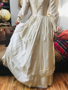 The back view of the Edwardian replica ivory satin wedding dress is shown - the voluminous skirt sweeps the floor