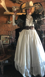 Cowgirl bride! A floor sweeping lace and satin edwardian wedding gown is teamed with a battered buff coloured cowgirl hat, antique lace shawl, brown leather corset belt and cowboy whip.