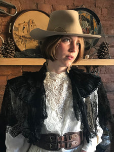 a beautiful prairie girl wears an Edwardian replica wedding dress in ivory satin and lace with a high lace neck. The dress is accessorised with an antique shawl of black lace, a battered cowboy hat and a brown leather belt. The prairie cowgirl bride is lit by a beam of warm sunlight, and stands in front of a rustic fireplace.