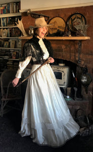 A prairie cowgirl bride smiles mischeviously as she swings her skirts. She is wering a bridal cowgirl hat and carrying a horde whip