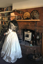 Back view - our prairie cowgirl bride stands in front of an old woodburner in a rustic boho room. Her floor sweeping ivory satin Edwardian style wedding dress is teamed with a cowgirl hat, antique black lace mantilla and brown leather waist cincher belt