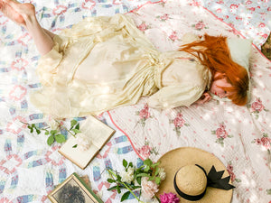 Back view of a pretty vintage wedding dress. The model lies on a picnic blanket in a way reminiscent of Alice in Wonderland - the moment when Alice falls asleep and drops her book . Red headed Alice
