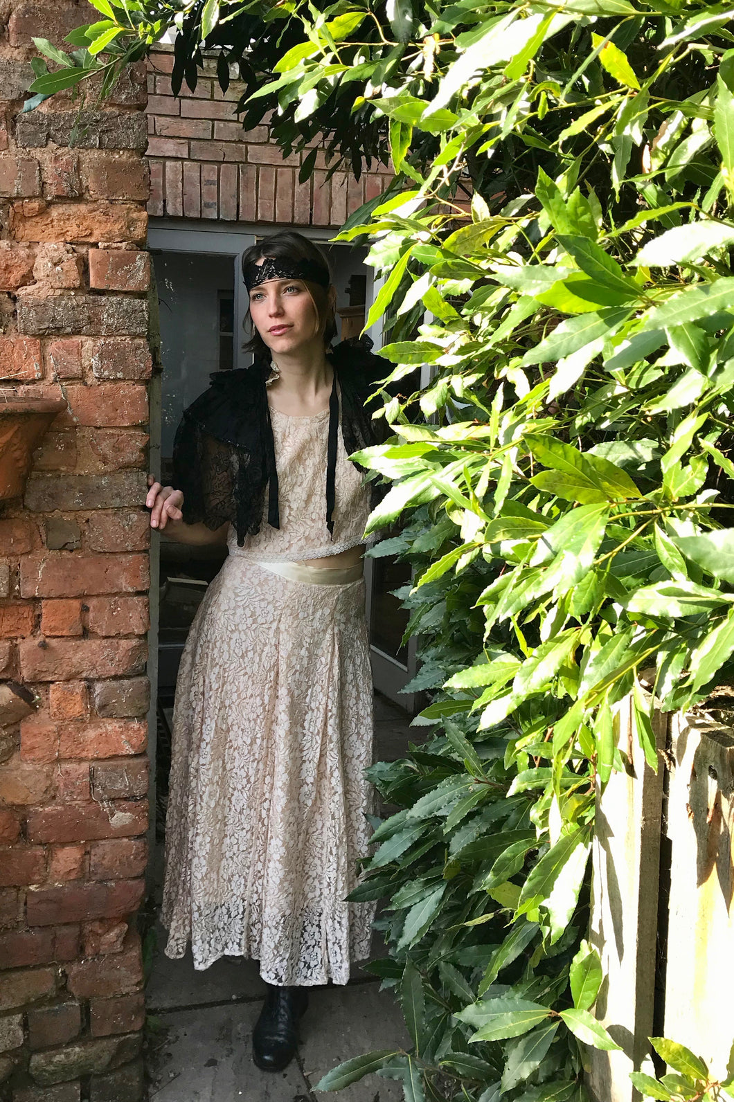 A pretty girl peers through a garden doorway. She is wearing 1940's separates made in shell pink lace. An antique black lace headband and cape complete the Bloomsbury style look.