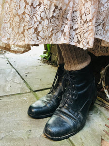 A close up of the soft pink lace at the hem of the skirt is shown , you can see that the vintage forties skirt is being worn with black lace up boots and woollen socks