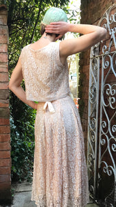 The back view of a 1940's vintage top and skirt are shown worn with a sweet 1920's cap. The outfit is made from early machine lace in a floral pattern