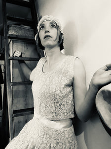 A black and white photo of a girl posing on a ladder wearing a 1940's wedding outfit - the separates appear like a dress when worn together, creating a Bloomsbury style wedding outfit
