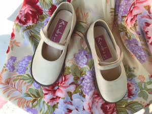 Cream silk bridesmaids shoes for a child are shown against a floral fabric