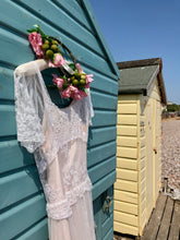 A white lace dress over a soft pink slip is hung on the door of a teal beachhut