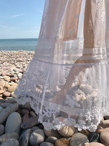 The fine details of antique Honiton lace can be seen on the skirt of an Edwardian wedding gown