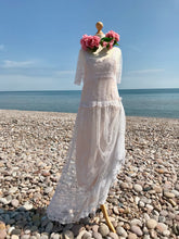 An Edwardian lace wedding dress with antique Honiton lace motifs, a dropped waist and elbow length sleeves is shown on pebble beach with floral crown of pink silk peonies