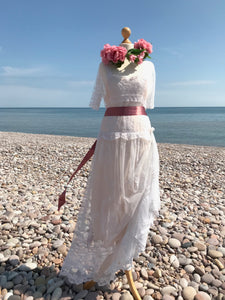 An Edwardian lace wedding dress is belted with a wide pink satin sash. The fine antique lace of the skirt is gathered and pinned at the hip
