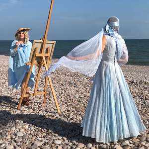 The back view of the pale blue flocked organza original vintage dress - worn by a model whose pale blue antique lace veil is blowing in the breeze. the model stands on a pebble beach. in the background, a second model stands at an easel in a sky blue swing coat from the same era