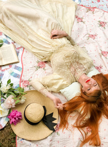A whimsical shot of a red headed model in a silk and lace Edwardian gown, lying on a picnic blanket surrounded by books, flowers and a large brimmed vintage hat. Charming Alice in Wonderland feel - cream silk wedding dress for a boho bride. Photography and styling by Louisa Currier for Days of Grace Vintage
