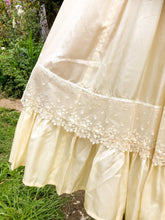 Close up of Edwardian antique lace on the skirt of an ivory silk replica Edwardian dress