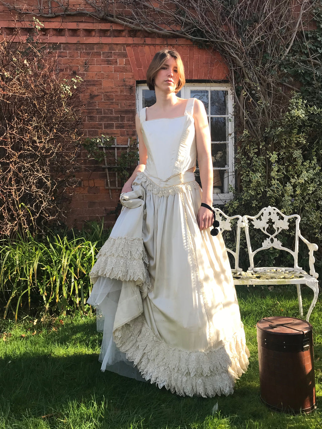 An elegant model stands in front of a red brick cottage, wearing a Victorian vintage ivory silk corset and skirt. She holds a gathered handful of the lace adorned skirt, showing it's fullness. A hat box sits on the grass beside her, and her expression is wistful. Worn together, the corset and skirt appear as one gown, perfect for a wedding dress.
