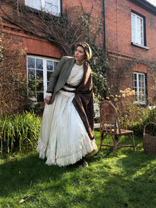 A whimsical bride wears her Victorian wedding dress with a 1930's tweed jacket, arran knit jumper, antique paisley shawl and double brown leather belt. She stands outside a red brick cottage with the sunlight streaming across her