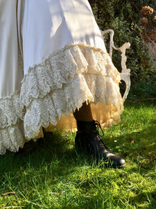 The details of the antique lace frills on the silk skirt are shown, delicate lace dripping in heavy folds. A laced boot and sturdy woollen stockings are just visible