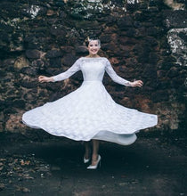 A model twirls wearing a 1950's wedding dress, the skirt twirling our around her waist like Marilyn Monroe - the dress is an ivory lace dress with long lace sleeves, a boat neck and a circle skirt