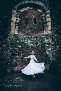 An authentic 1950's wedding dress with long lace sleeves from days Of Grace Vintage in Devon. The model is shown twirling in front of the ivy covered walls of Exeter castle
