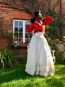 A striking model wears a red Victorian military jacket over an ivory Victorian wedding dress. The look is finished with a battered black top hat and antique lace veil. The look could be described as steam punk bride.